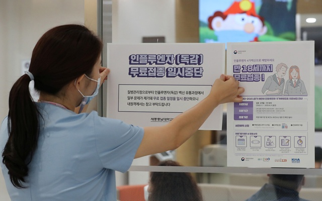 A health worker attaches a notice for suspension of influenza vaccination programmes on an entrance of a hospital in Sejong, South Korea, September 22, 2020. Yonhap via REUTERS