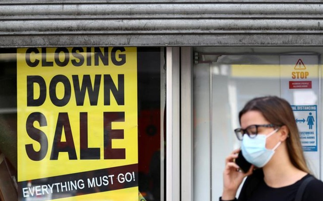 A woman wearing a protective mask speaks on the phone in front of a closed down store, as the spread of the coronavirus disease (COVID-19) continues, in London, Britain Jul 16, 2020. REUTERS/FILE