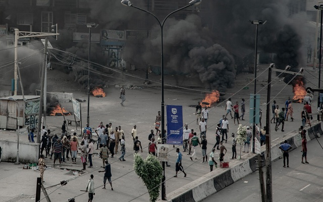 People are seen near burning tires on the street, in Lagos, Nigeria October 21, 2020, in this image obtained from social media. UnEarthical/via REUTERS