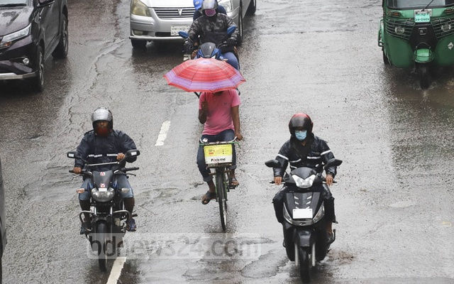 A man pedals a bicycle with an umbrella in one hand in Dhaka's Kalabagan during rains triggered by a deep depression over the Bay of Bengal on Oct 22, 2020. Photo: Asif Mahmud Ove
