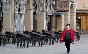 A masked woman walks past a closed bar after the Navarran local government limited all non-essential movement in and out of the region for two weeks starting Thursday, amid the coronavirus outbreak, Pamplona, Spain, October 22, 2020. Reuters