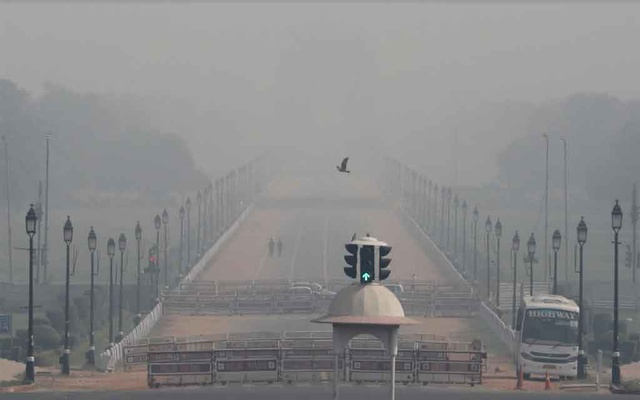 People walk near India Gate on a smoggy morning in New Delhi, India, October 22, 2020. REUTERS