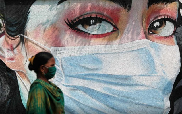 A woman walks past a graffiti of a girl wearing a protective mask amidst the spread of the coronavirus disease (COVID-19) in Mumbai, India, Oct 23, 2020. REUTERS