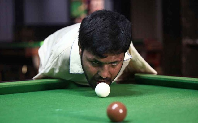 Muhammad Ikram, 32, who was born without arms, plays snooker with his chin at a local club in Samundri, Pakistan, October 20, 2020. Picture taken October 20, 2020. REUTERS/Mohsin Raza