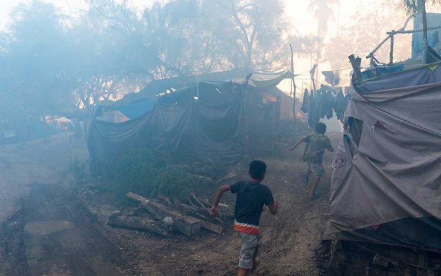 Children run through a migrant camp in Matamoros, Mexico, across the border from Brownsville, Texas, as it is being fumigated, Aug 5, 2020. The squalid tent camp on the border is the result of President Donald Trump's unprecedented limits on asylum. Some people have waited in filthy conditions for more than a year to obtain refuge in the US (Ilana Panich-Linsman/The New York Times)