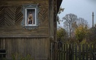 Marina Udgodskaya, recently elected as the mayor of Povalikhino, Russia, looks out the window of her home in the tiny village some 300 miles northeast of Moscow, Oct 15, 2020. (Emile Ducke/The New York Times)