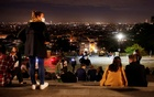 People enjoy the view from Montmartre a few minutes before the nightly curfew imposed to curb the spread of the coronavirus, in Paris, France, Oct 22, 2020. REUTERS