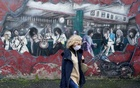 FILE PHOTO: A woman walks past a wall mural during the resurging coronavirus outbreak in Galway, Ireland, October 20, 2020. REUTERS