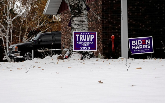 Yard signs supporting US President Donald Trump and Democratic presidential candidate Joe Biden and his running mate Kamala Harris are seen in front of the same suburban home in Fargo, North Dakota, US, October 25, 2020. REUTERS