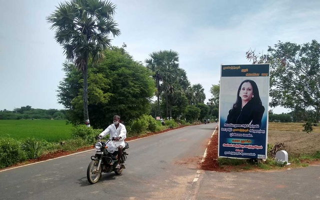 A man drives past a banner of US Democratic vice presidential nominee Kamala Harris at the entrance to the village of Thulasendrapuram, where Harris' maternal grandfather was born and grew up, in the southern Indian state of Tamil Nadu, India, Oct 25, 2020. REUTERS