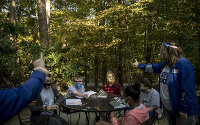 Teachers lead their class in a singalong at Garvan Woodland Gardens at the University of Arkansas in Hot Springs on Oct. 7, 2020. To combat the coronavirus, schools across America moved students outdoors. (Andrea Morales/The New York Times)