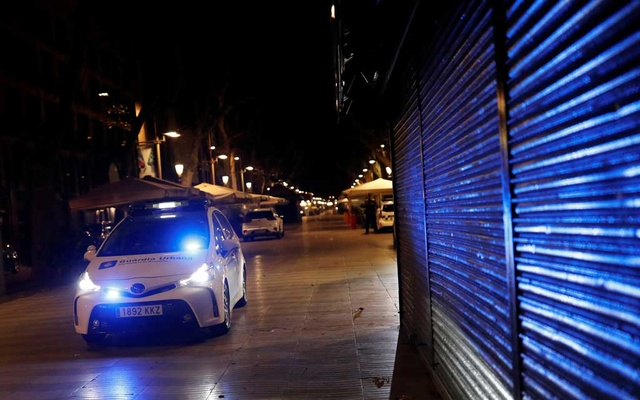 Police officers patrol in a police vehicle during the first day of the night-time curfew set as part of a state of emergency in an effort to control the outbreak of the coronavirus disease (COVID-19), in Barcelona, Spain October 26, 2020. REUTERS