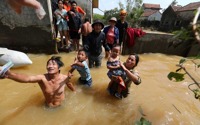 Residents get money from a volunteer at a flooded area in Quang Binh province, Vietnam October 23, 2020. Thanh Dat/VNA via REUTERS