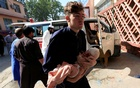 FILE PHOTO: A man carries an injured child at a hospital after a truck bomb blast, in Jalalabad, Afghanistan October 3, 2020. REUTERS/Parwiz/File Photo