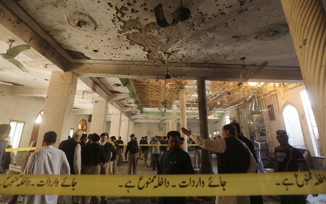 Police officers and officials survey the site of a bomb blast at a religious seminary in Peshawar, Pakistan Oct 27, 2020. REUTERS