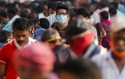 A man wearing a protective mask is seen among people at a crowded market amidst the spread of the coronavirus disease in Mumbai, India, October 29, 2020. REUTERS