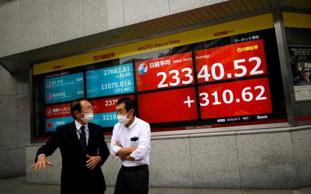 FILE PHOTO: Men wearing protective face masks chat in front of a screen displaying Nikkei share average and world stock indexes outside a brokerage, amid the coronavirus disease (COVID-19) outbreak, in Tokyo, Japan October 5, 2020. REUTERS