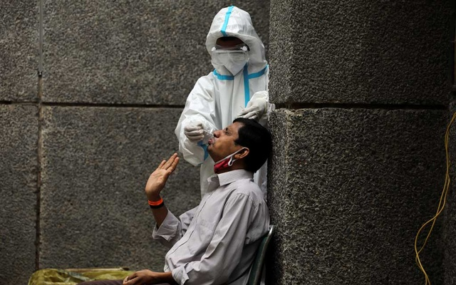 A healthcare worker wearing personal protective equipment (PPE) collects a swab sample from a man amidst the spread of the coronavirus disease (COVID-19), at a testing centre in New Delhi, India October 29, 2020. REUTERS