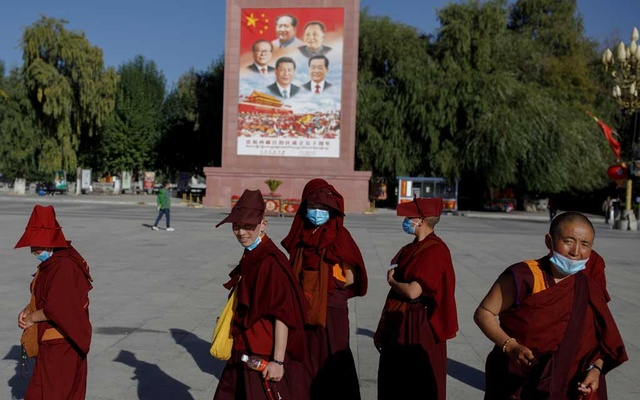 Buddhist nuns walk past a poster showing Chinese President Xin Jinping and former Chinese leaders Jiang Zemin, Mao Zedong, Deng Xiaoping and Hu Jintao in Potala Palace square in Lhasa, during a government-organised tour of the Tibet Autonomous Region, China, Oct 15, 2020. REUTERS