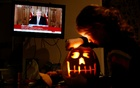 8-years-old Alice Wilkinson carves a Halloween pumpkin at her home as Britain's Prime Minister Boris Johnson speaks at a news conference, amid the outbreak of the coronavirus disease (COVID-19) in Manchester, Britain, October 31, 2020. Reuters