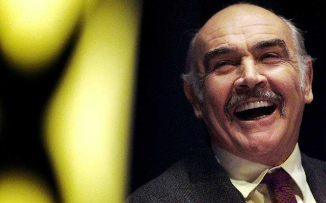 FILE PHOTO: Actor Sean Connery laughs as he listens to a speech by Alex Salmond at a Scottish National Party rally at the Edinburgh International conference centre April 26. REUTERS/Jeff J Mitchell/File Photo