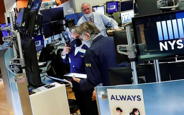 Traders wearing masks work, on the first day of in person trading since the closure during the outbreak of the coronavirus disease (COVID-19) on the floor at the New York Stock Exchange (NYSE) in New York, US, May 26, 2020. REUTERS