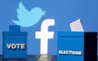 3D-printed ballot boxes are seen in front of Facebook and Twitter logos. Reuters