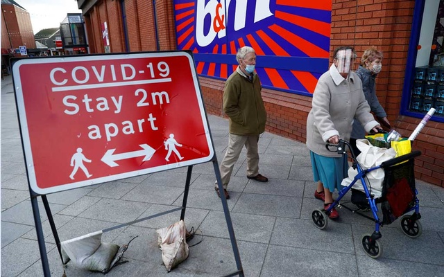 People wearing protective face coverings walk past a social distancing sign, as the spread of the coronavirus disease (COVID-19) continues, in Northwich, Britain, Nov 10, 2020. REUTERS
