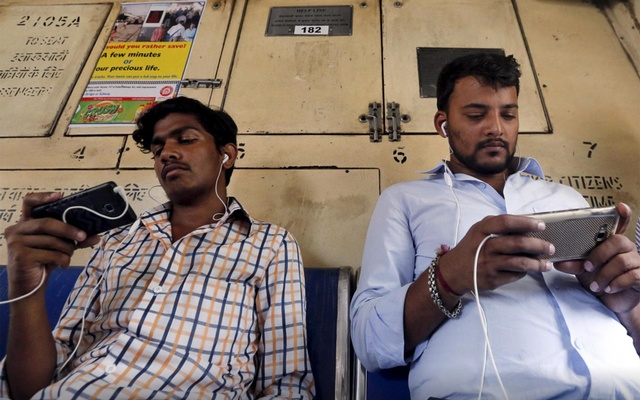 Commuters watch videos on their mobile phones as they travel in a suburban train in Mumbai, India, April 2, 2016. REUTERS