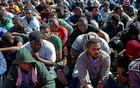 Migrants sit at a security checkpoint after they were intercepted by Libya's Government of National Accord (GNA)'s Interior Ministry before attempting a journey to Europe, in the city of Khoms, Libya November 3, 2020. REUTERS