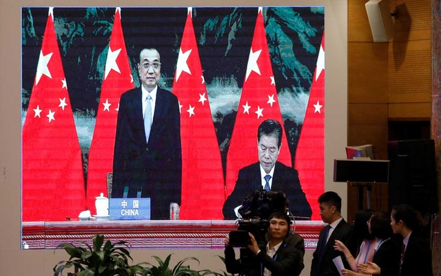 Media crew stand next to a screen showing Chinese Minister of Commerce Zhong Shan (R) signing next to Chinese Premier Li Keqiang during the virtual signing ceremony of the Regional Comprehensive Economic Partnership (RCEP) Agreement during the 37th ASEAN Summit in Hanoi, Vietnam, Nov 15, 2020. REUTERS
