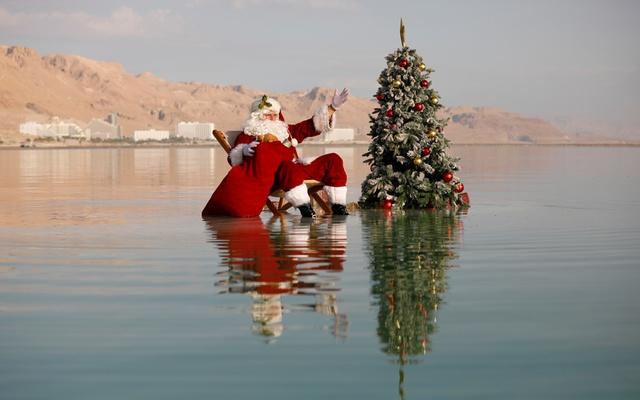 Issa Kassissieh, wearing a Santa Claus costume, gestures as he poses for a picture while sitting next to a Christmas tree on a salt formation in the Dead Sea, in an event organised by Israel's tourism ministry, as Israel gears up for the holiday season, amid the coronavirus disease (COVID-19) crisis, near Ein Bokeq, Israel November 15, 2020. Reuters