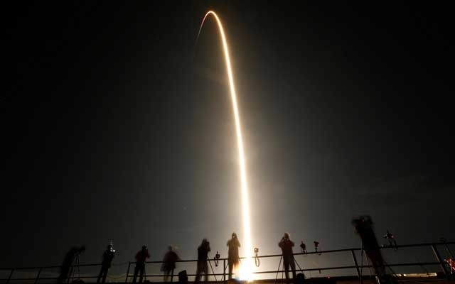 People watch as a SpaceX Falcon 9 rocket, topped with the Crew Dragon capsule, is launched carrying four astronauts on the first operational NASA commercial crew mission at Kennedy Space Centre in Cape Canaveral, Florida, US November 15, 2020. REUTERS