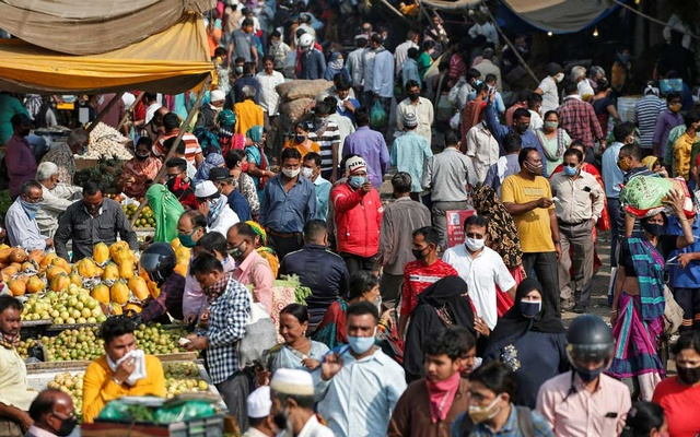 A health worker takes the temperature of shoppers at a crowded market amid the spread of the coronavirus disease (COVID-19), in Ahmedabad, India, Nov 20, 2020. REUTERS