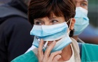 A health worker, wearing protective face masks, smokes a cigarette during a demonstration in Nice as part of a nationwide day of actions to urge the government to increase staff as hospitals fill once again with COVID-19 patients, France, October 15, 2020. The slogan reads