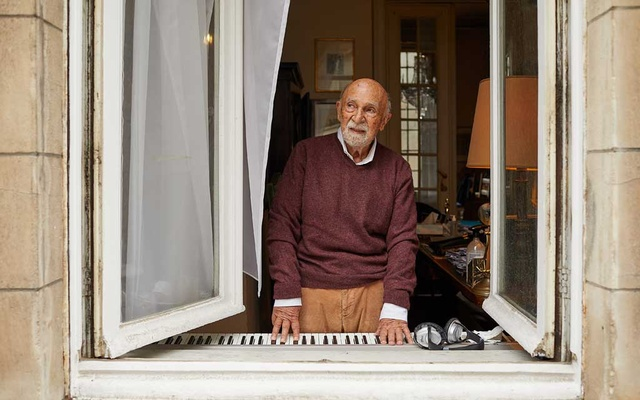 Simon Gronowski, a Holocaust survivor, at the electric piano he moved beneath a window of his apartment at the height of the first wave of the coronavirus in Europe, in Brussels, Oct 22, 2020. Gronowski began to play regularly, filling the leafy streets with jazz notes and bringing relief to his besieged neighbours throughout the lockdown that lasted into late May. (Ksenia Kuleshova/The New York Times)