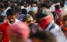 FILE PHOTO: A man wearing a protective mask is seen among people at a crowded market amidst the spread of the coronavirus disease (COVID-19) in Mumbai, India, October 29, 2020. REUTERS/Francis Mascarenhas