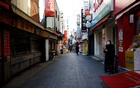 A shopkeeper waits for customers at an empty shopping district amid the coronavirus disease (COVID-19) pandemic in Seoul, South Korea, Nov 23, 2020. REUTERS