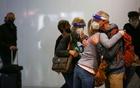 Travellers wearing protective face masks and face shields to prevent the spread of the coronavirus disease (COVID-19) hug after departing a flight at the airport in Denver, Colorado, US, November 24, 2020. Reuters