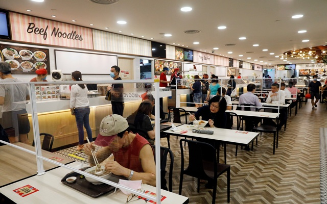 People eat at a table installed with plexiglass dividers at a food court in Singapore as the city state enforces social distancing to fight the spread of the coronavirus disease (COVID-19), Jun 19, 2020. REUTERS/FILE