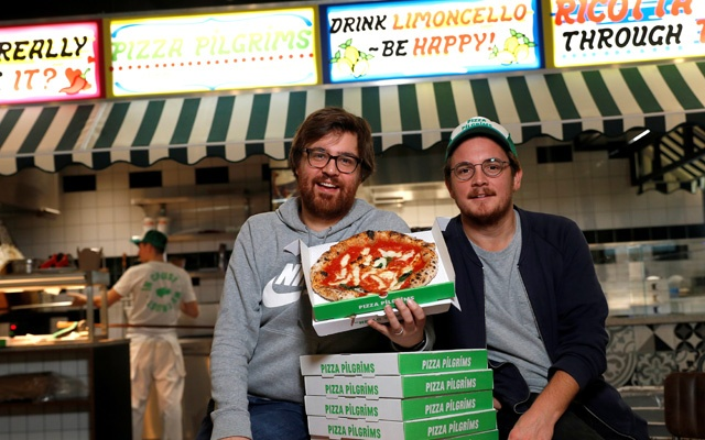 Co-founders of Pizza Pilgrims, brothers Thom (L) and James Elliot, pose for a photograph in one of their restaurants amid the coronavirus disease (COVID-19) outbreak in London, Britain, November 20, 2020. REUTERS