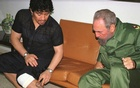 Argentine football legend Diego Maradona, then in Cuba undergoing rehabilitation for cocaine abuse, shows Cuban President Fidel Castro a tattoo of him on his leg, inside Revolution Palace in Havana, in this file photo from October 29, 2001. Reuters