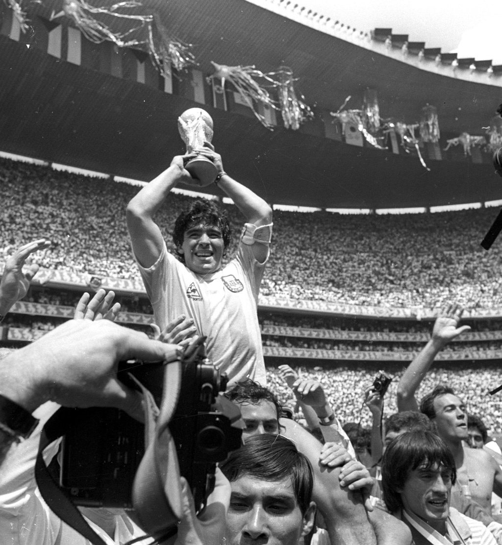 Argentine star Diego Maradona holds up the World Cup trophy as he is carried off the field after Argentina defeated West Germany 3-2 to win the World Cup football championship in Mexico City June 29, 1986. Reuters