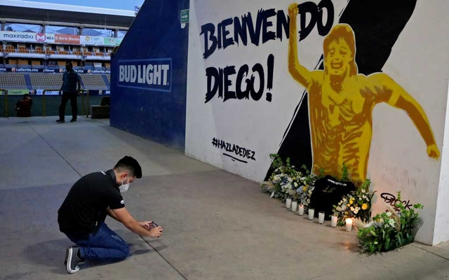 A fan takes a photo of a mural showing late Argentine soccer legend Diego Armando Maradona, who was the team's coach, at the Dorados stadium in Culiacan, Sinaloa state, Mexico, Nov 25, 2020. REUTERS