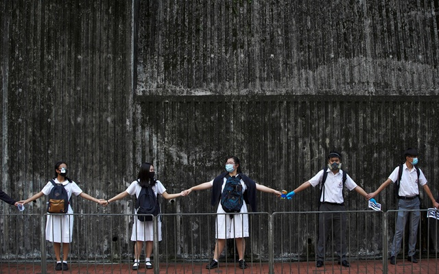 FILE PHOTO: Secondary school students hold hands as they form a human chain in Hong Kong, China, September 12, 2019. REUTERS