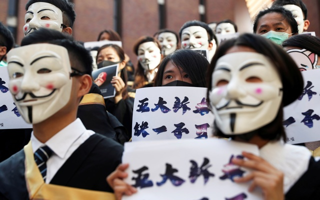 University students wearing Guy Fawkes masks pose during a news conference to support anti-government protests before their graduation ceremony at the Hong Kong Polytechnic University in Hong Kong, China, November 5, 2019. REUTERS