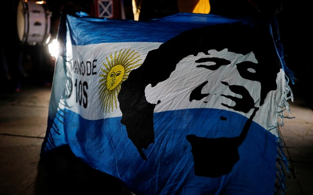 A soccer fan holds an Argentine flag with the face of late Argentine soccer legend Diego Armando Maradona painted on it during a tribute to him the day after his death, in Barcelona, Spain, November 26, 2020. REUTERS