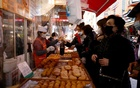 Women buy donuts at a traditional market amid the coronavirus disease (COVID-19) pandemic in Seoul, South Korea, Nov 26, 2020. REUTERS