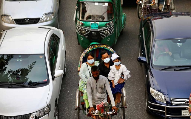 People are seen wearing protective mask while riding on a rickshaw in Dhaka, Bangladesh, Nov 19, 2020. REUTERS
