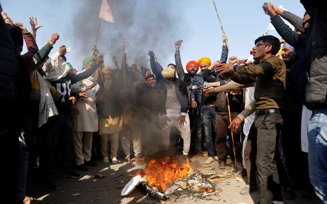 Farmers shout slogans as they burn an effigy during a protest against the newly passed farm bills at Singhu border near Delhi, India, Nov 28, 2020. REUTERS